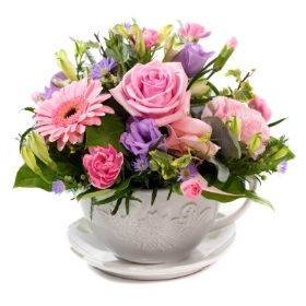 pinks pastels mothers day arrangement of flowers in a tea cup